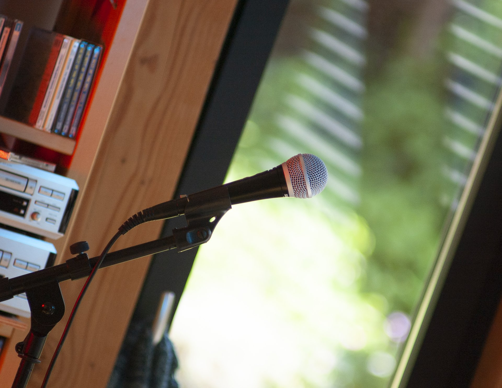 A microphone backlit by sunshine and light... music and CDs on shelving can be glimpsed in the corner of the shot.