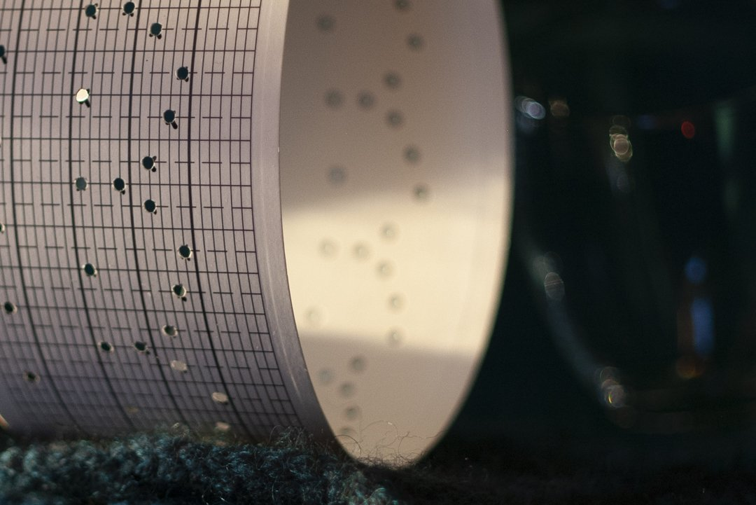 a componium punch-card roll pictured beside the edge of some handknitted fabric