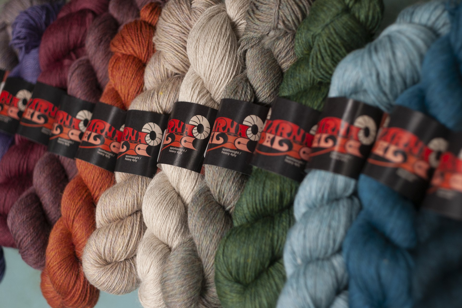 Yarnadelic yarns, arranged from left to right, reds and purples through orange, neutral, undyed, green and blue... they are wound in skeins with their label (designed by a record-label designer) and photographed on a bench against the duck-egg blue colour of the factory floor.